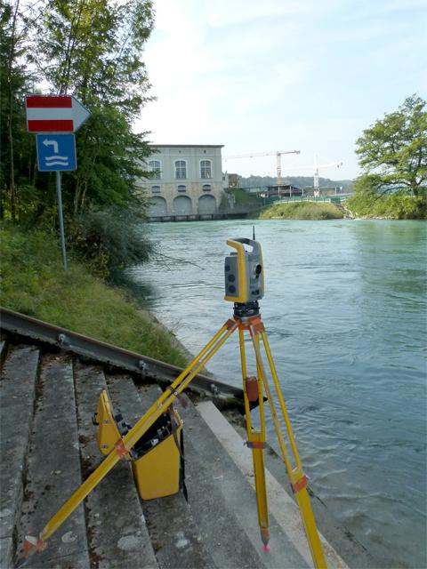 Messgerät am Fluss, Wasserkraftwerk im Hintergrund